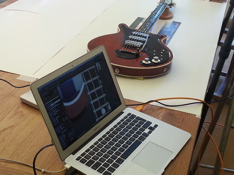 Here the team is setting up a full shot of the Red Special. Photographed on a white background, the camera is suspended above the guitar and the images captured displayed on the laptop in the foreground
